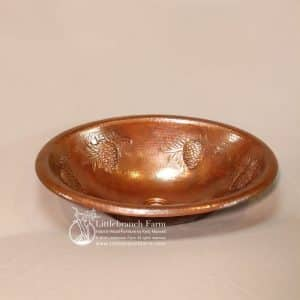 Hammered copper sink with pinecone design.