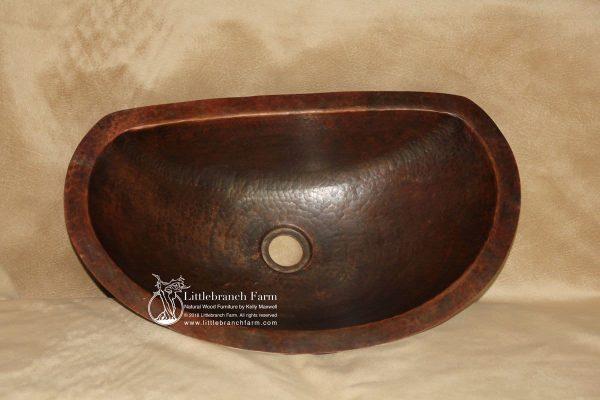 Natural cooper vessel sink in oval shape.