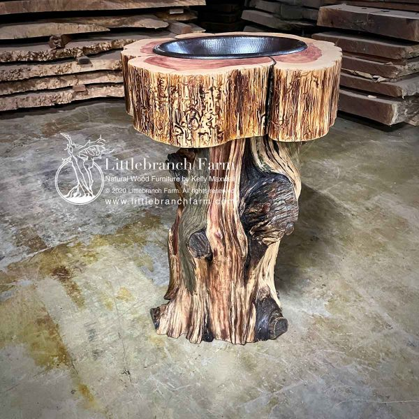 Tree stump vanity with copper sink.