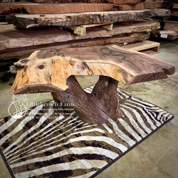 Rustic wood slab coffee table on zebra rug.