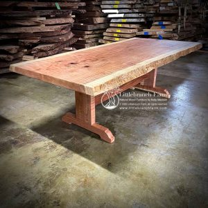 Redwood slab dining table with wood trestle base.