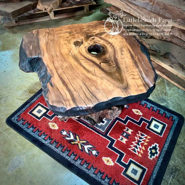 Fire chard carved live edge redwood slab on red rug.