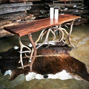 Rustic sofa table on cowhide rug.