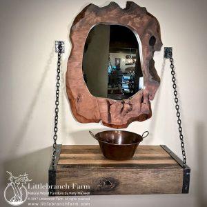 Floating vanity with burl wood mirror.